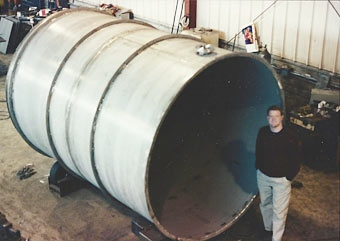 Patrick Smith, VP, inspecting large stainless steel waste water treatment tank prior to loading.